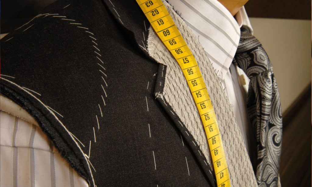 Tailor with measuring tape over shoulder